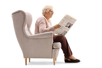 Mature woman sitting in an armchair and reading a newspaper