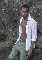 Photo shoot for a black handsome guy on the rocky shore of the ocean