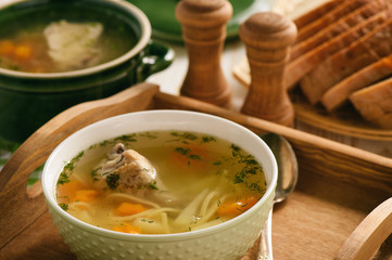Chicken soup in bowl on wooden tray.