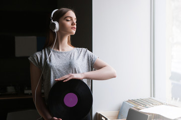 Female Dj. Vinyl records background. Modern youth lifestyle, thoughtful girl enjoying listen to music