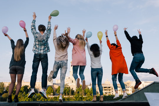 Birthday party celebration. Students company jumps. Young people on holiday, sky background, friendship concept