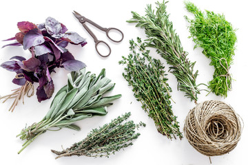 drying fresh herbs and greenery for spice food on white kitchen desk background top view pattern
