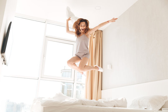 Young funny woman jumping on bed with pillow