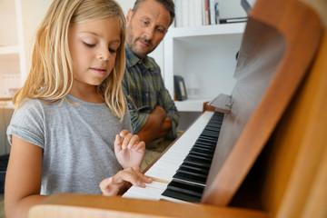 Little girl with teacher playing piano