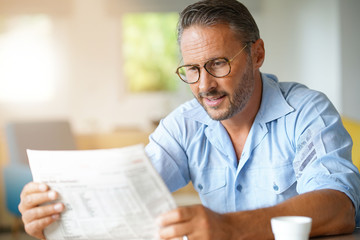 Portrait of mature man with eyeglasses reading newspaper