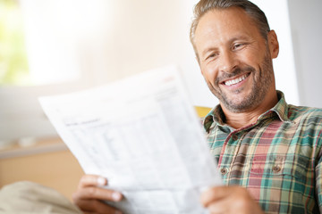 Cheerful mature man reading newspaper at home