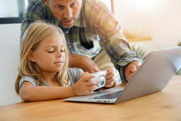 Little girl with daddy looking at pictures on computer