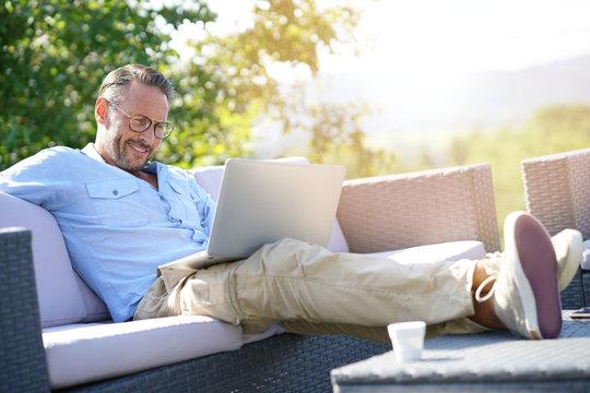 Smiling mature man using laptop, relaxing in outdoor sofa