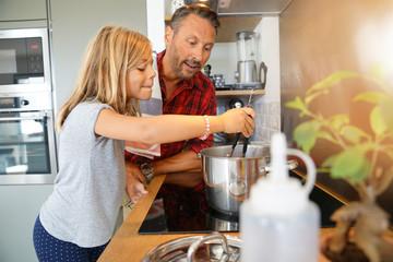Papa met dochter die samen kookt in de thuiskeuken