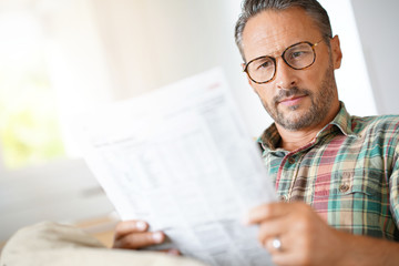 Mature man with eyeglasses reading newspaper