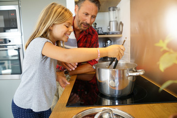 Keuken foto achterwand Koken Daddy with daughter cooking together in home kitchen