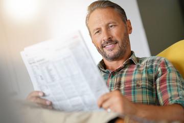 Cheerful mature man reading newspaper at home