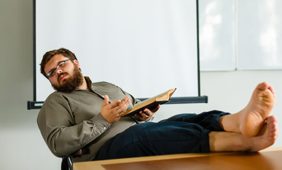 the teacher reads the book, the bare feet on the table and smiling. on a light studio background