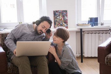 A young couple listen to music from a laptop computer