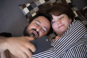 Young couple relaxing on couch and taking selfie with a smartphone