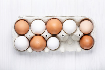 Pack of farm chicken eggs in cardboard container on white.