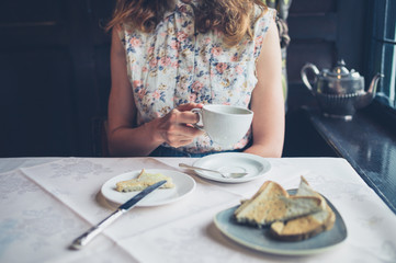 Young woman drinking coffee and eating toast
