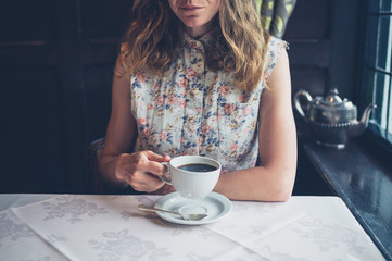 Woman at table by window drinking coffee