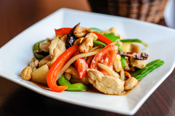 Stir-Fried Cashew Chicken, Slices of chicken breast stir-fried with cashew nuts, peapods, pineapple, onions, tomato ,and bell peppers.