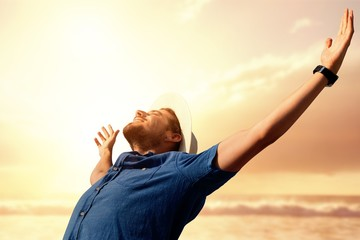 Composite image of happy man raising his arms up