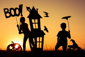 Wall Mural - Happy brother and  sister playing outdoors at the sunset time.