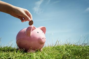 Child hand saving money in piggy bank
