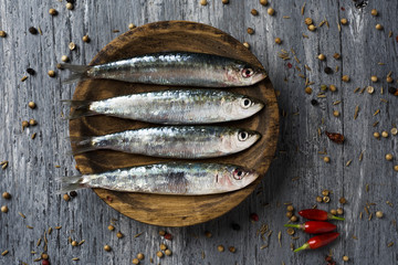 raw sardines on a rustic wooden table
