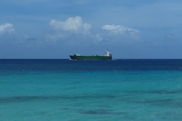 cargo ship on the horizon in tranquil tropical sea