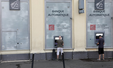 Customers use ATM machines at a Caisse d'Epargne bank branch in Nice