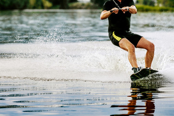 male wakeboarder rides on lake in wakeboard splashes of water Wall mural