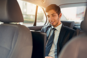 Young businessman working inside the car