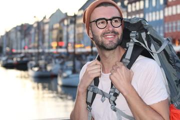 Backpacker smiling in the epic Nyhavn, Copenhagen, Denmark.