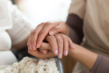 Caregiver holding senior woman's hands
