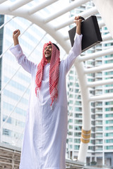 Success and Happiness concept, Portrait of Smiling Arab Middle Eastern Businessman successful project.He holding briefcase and Arms stretched glad