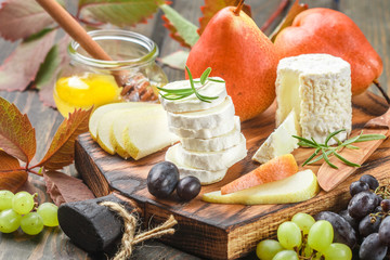 Goat cheese with fruit and honey. Camembert. Bree. Grape, pear and rosemary. Gourmet wine snacks. Selective focus