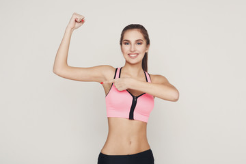 Smiling fitness woman shows her muscular hand