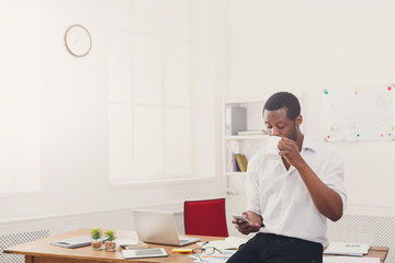 Young black businessman with mobile phone in modern white office
