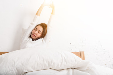 Woman stretching in bed after wake up in the morning at home