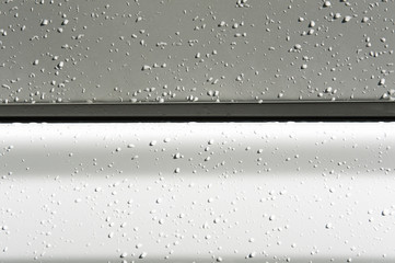 Rain drops on the side panel of a truck create an abstract image.