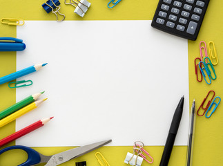 Colorful stationery on yelow background - calculator, scissors,  crayon, pencil, pen, white paper