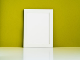 Blank white frame on a white table against the olive colored wall with copy space