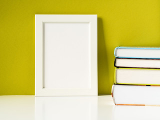Blank white frame and stack of books on a white table against the olive colored wall with copy space