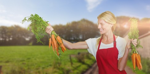Composite image of smiling young woman holding carrot
