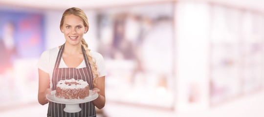 Composite image of portrait of young woman holding cake