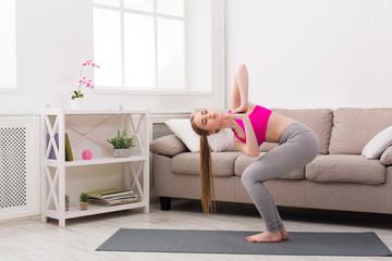 Woman training yoga in twisting awkward pose.