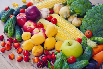 Autumn harvest vegetables. Vegetable composition. Fresh vegetables: broccoli, carrot, corn, cucumber, garlic, potatoes, salad, tomato, basil. Organic Vegetables. Fruits: cherry, peaches, apricots.