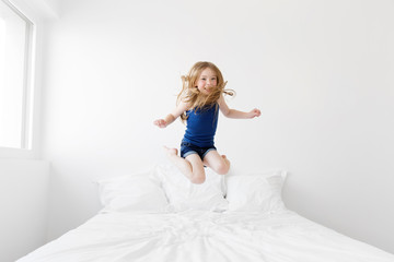 Smiling young girl jumping on white bed