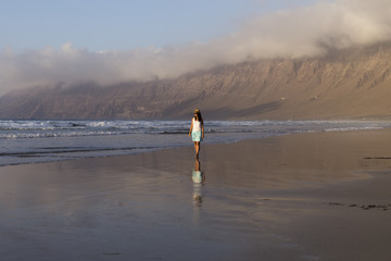 young beautiful woman walking by the seashore in Lanzarote, Canary islands. Summer. reflection in the water. lifestyle
