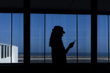 silhouette of a young woman using mobile phone in the airport. Travel concept.