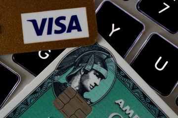 An American Express and a Visa credit cards are seen on a computer keyboard in this picture illustration